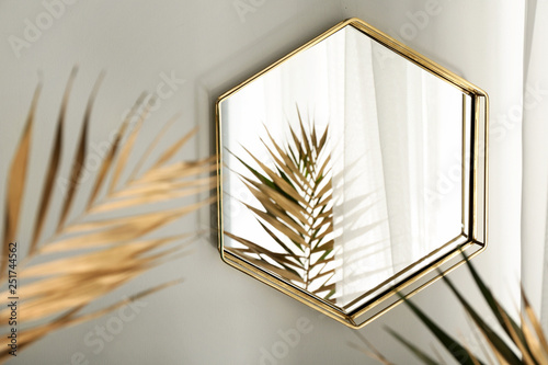 Mirror and golden tropical leaves in room