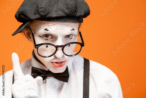 Fotografie, Obraz  Portrait of a pantomime with white facial makeup in eyeglasses showing expressiv