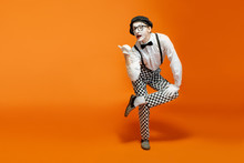 Emotional Pantomime With White Facial Makeup Showing Empty Space On The Orange Background, Advertising Something