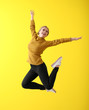 Jumping young woman on color background