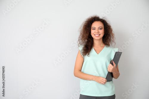 Fototapeta Portrait of young businesswoman on light background obraz na płótnie