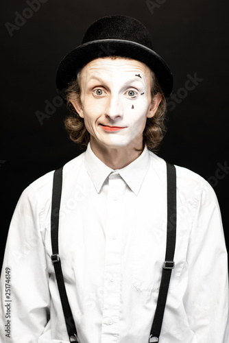 Fotografie, Tablou  Portrait of a pantomime with a make-up on the one side of his face on the black background
