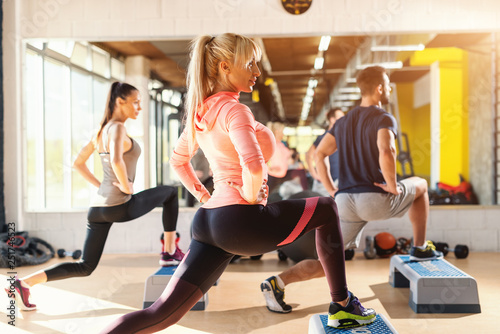 Fototapeta Group of people with healthy habits doing exercises for legs on steppers. Gym interior. obraz