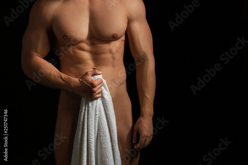 fototapeta na lodówkę Muscular sexy bodybuilder with towel on dark background