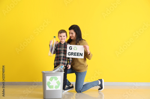 Mother and son holding paper sheet with text GO GREEN and trash bin against color wall Canvas Print