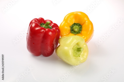 Fotografie, Obraz Three delicious ripe Bulgarian peppers, lime, red, orange, with green tails in t