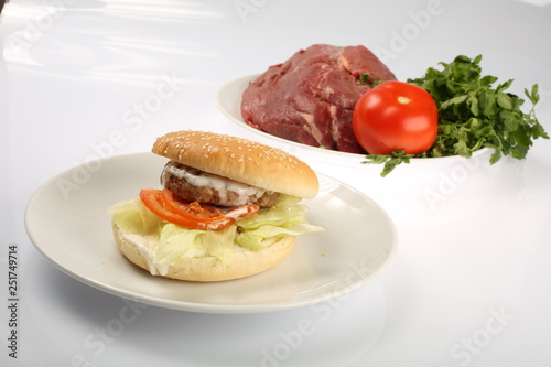 Fotografia cheeseburger with bacon and beef patty on a plate with vegetables, bell pepper,