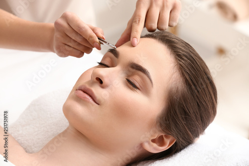 Canvas Print Young woman undergoing eyebrow correction procedure in beauty salon