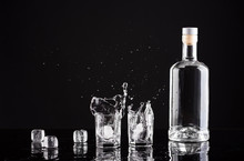 Bottle Of Vodka With Glasses And Splashes On A Black Background