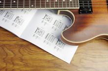 Electric Guitar And An Open Book With Guitar Chords.
