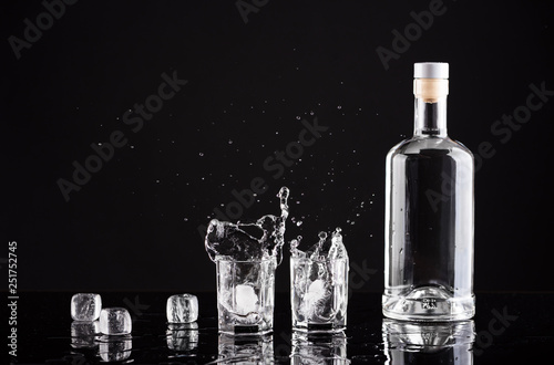 Obraz na płótnie bottle of vodka with glasses and splashes on a black background