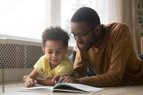 Happy black father and toddler son reading book at home