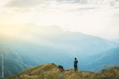 Fototapeta Instagram filter young man Asia tourist at mountain is watching over the misty and foggy morning sunrise, travel Trekking obraz na płótnie