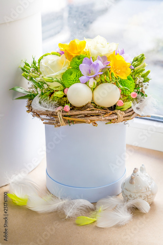Fotografía  Easter arrangement of flowers and eggs in a cylindrical blue box is on the windo