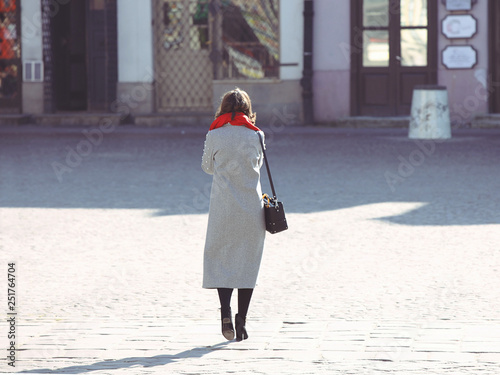 Fotografía  A woman in a stylish autumn outfit is walking on the pavement of the ancient city