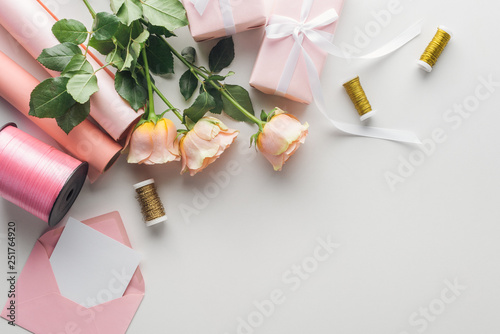 top view of roses, rolls of paper, wrapped gifts, envelope, greeting card and spools of thread on grey background