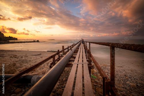 Foto auf Gartenposter Strand old wooden pier at sunset
