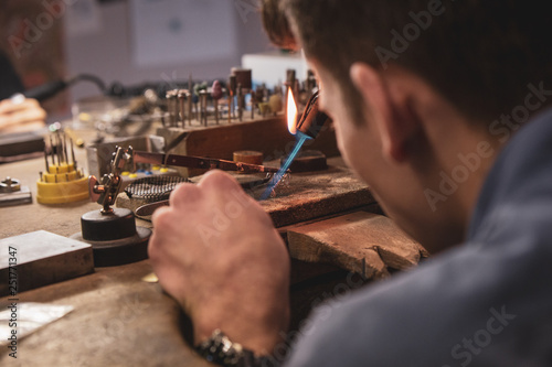 Jeweller crafting on a wooden work bench with a blowpipe Wallpaper Mural