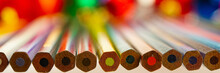 Colored Pencils Lie On The Surface Of The Table And Blurred Background.