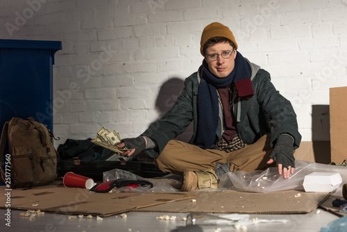 Photo homeless man holding money while sitting on rubbish dump