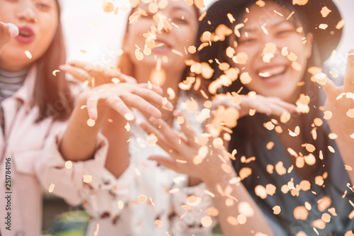 Stampa su Tela  Blurred asian friends having fun throwing confetti at party outdoor - Young tren