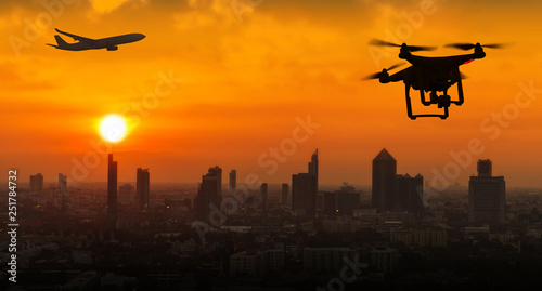 Fotografie, Obraz  Silhouette of drone flying near an airport with airplane, no drone zone concept