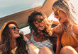 canvas print picture - Three female friends enjoying traveling in the car. Sitting in rear seat and having fun on a road trip.