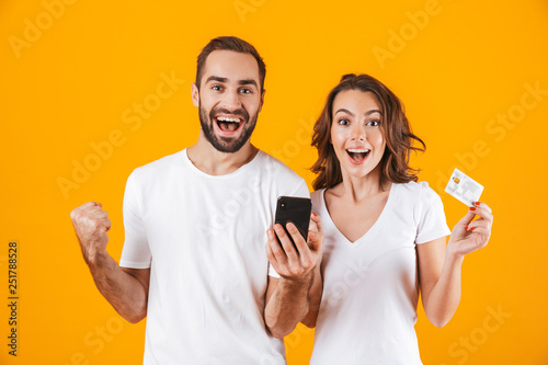Fotografía  Image of positive couple man and woman using cell phone and credit card, isolate