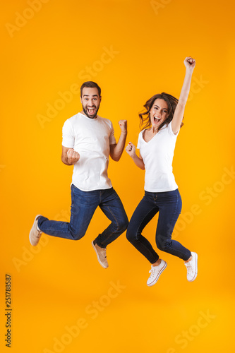 Full length photo of rejoicing couple screaming in surprise while jumping, isolated over yellow background