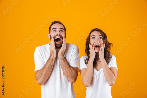 Image of happy people man and woman in basic clothing screaming in surprise and Wallpaper Mural