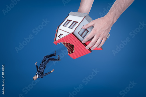 Close-up of man's hands holding house with hole in roof upside down and dropping out little businessman Canvas Print