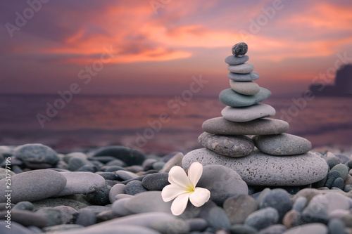 Acrylic Prints Stones in Sand Pyramid of stones and a white flower on the beach by the sea on the background of a colorful sunset