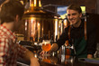 Barmen smiling, giving glass of beer to client. Man sitting at bar counter and waiting for beer. Barmen of beer house wearing in black shirt and apron looking at client.
