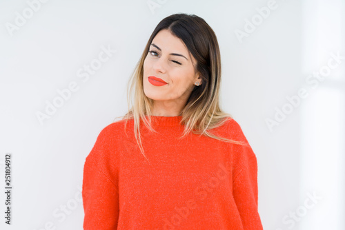 Young woman wearing casual red sweater over isolated background winking looking at the camera with sexy expression, cheerful and happy face Wallpaper Mural
