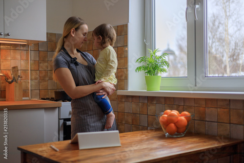 Fotografie, Obraz Mother with her baby girl looking for recipe on digital tablet