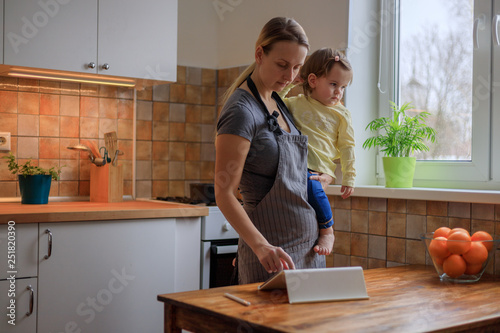 Fototapeta Mother with her baby girl looking for recipe on digital tablet