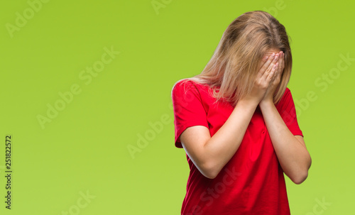 Fotografia Young caucasian woman over isolated background with sad expression covering face with hands while crying