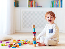 Cute Toddler Baby Boy Playing With Wooden Blocks, Building A High Tower