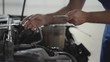 Hands of auto master working with the car with an open hood and verifies information on his phone. Skillful man in uniform fixing automobile in car repair station