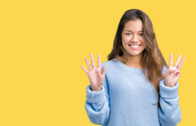 Young Beautiful Brunette Woman Wearing Blue Winter Sweater Over Isolated Background Showing And Pointing Up With Fingers Number Eight While Smiling Confident And Happy.