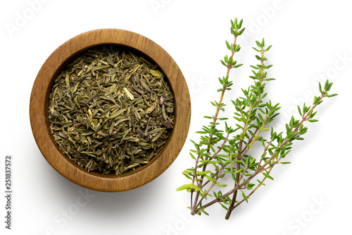Obraz na plátně Dried rubbed thyme in a dark wood bowl next to fresh thyme sprig isolated on white from above
