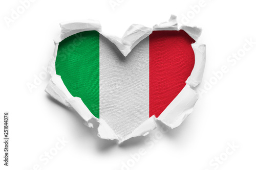 Heart shaped hole torn through paper, showing satin texture of flag of Italy. Isolated on white background