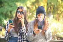 Two Girls Smoking Cigarettes A...