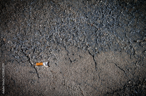 Fotografie, Obraz  cigarette but on cracked damaged concrete sidewalk metaphor for diseased and dam