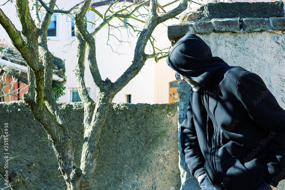 Fototapeta Unknown man in hood as robber or burglar or thief is spying around property with a plan to do illegal activity