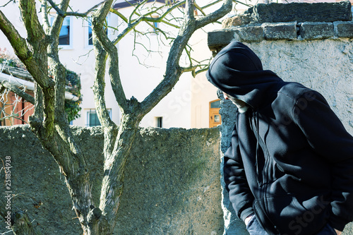 Unknown man in hood as robber or burglar or thief is spying around property with Fototapet