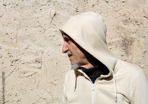 Fotografía  Unknown man in hood as robber or burglar or thief is spying around property with