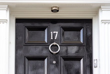 House Number Seventeen In Silver Numerals On A Black Wooden Door With Silver Knocker, 17