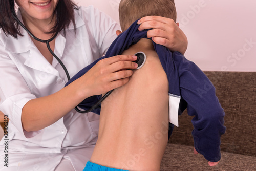 Photo Pediatrician listening boy's breathing with stethoscope on back