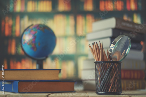 Foto  Textbooks,  globe and pencils on a wooden background